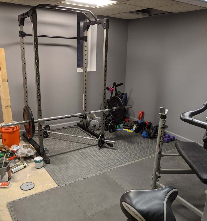 Power rack for weightlifting, set up in a basement.